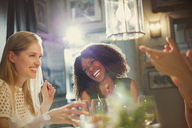 Laughing women friends clapping and dining at restaurant table - CAIF10778