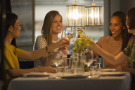 Smiling women friends toasting white wine glasses dining at restaurant table - CAIF10793