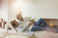Smiling pregnant couple laying on living room sofa near fireplace - CAIF10802