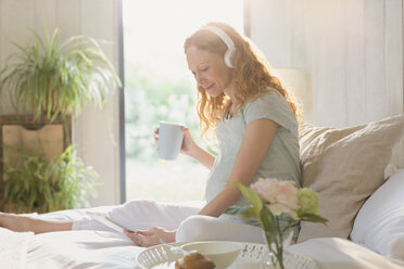 Pregnant woman drinking coffee and listening to music with headphones and digital tablet on bed - CAIF10814