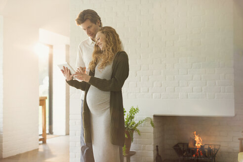 Pregnant couple using digital tablet near fireplace in living room - CAIF10835