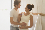 Pregnant couple brushing teeth in bathroom - CAIF10847