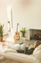 Comfortable pregnant woman laying reading book near fireplace in living room - CAIF10853