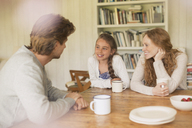 Family drinking tea and talking at dining table - CAIF10868