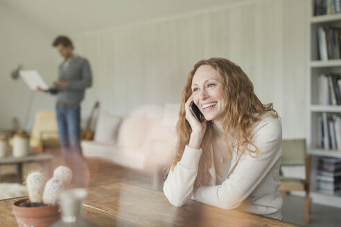 Smiling woman talking on cell phone at dining table - CAIF10874