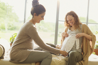 Pregnant women looking at baby clothing - CAIF10886