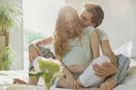 Affectionate pregnant couple kissing in pajamas on bed in sunny bedroom - CAIF10889