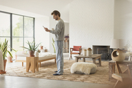 Man in pajamas drinking coffee and using digital tablet in living room - CAIF10892