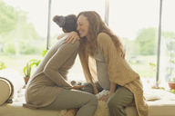 Affectionate pregnant women hugging - CAIF10901