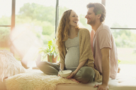 Smiling pregnant couple eating and talking - CAIF10910