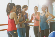 Smiling women talking and drinking water in sunny gym studio - CAIF10928