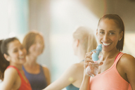 Portrait smiling woman drinking water in exercise class gym studio - CAIF10943