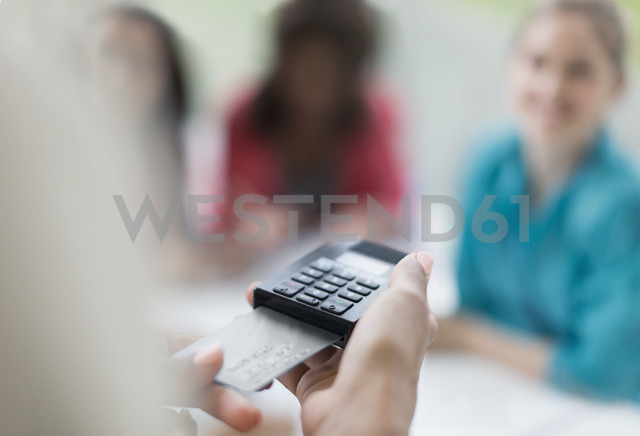 Close up waitress using credit card reader at cafe table - CAIF10949