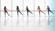 Women exercising at barre in exercise class gym studio - CAIF10952
