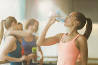 Woman drinking water in exercise class gym studio - CAIF10964