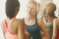 Smiling women talking in exercise class gym studio - CAIF10967