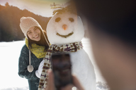 Man photographing woman with snowman - CAIF11018