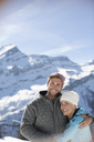 Portrait of smiling couple hugging below mountain - CAIF11027