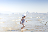 Girl wading in surf on beach - CAIF11057