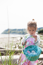 Girl gathering Easter eggs in basket on beach - CAIF11060