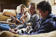 Brothers and sisters holding puppies on sofa - CAIF11078