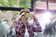 Young woman trying virtual reality simulator glasses at technology conference - CAIF11111