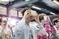 Audience trying virtual reality simulator glasses at technology conference - CAIF11138