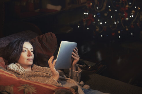 Woman using digital tablet relaxing on sofa in living room near Christmas tree - CAIF11141
