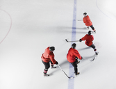 Hockey team in red uniforms skating on ice - CAIF11144
