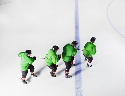 Hockey team in green uniforms skating in a row on ice - CAIF11147