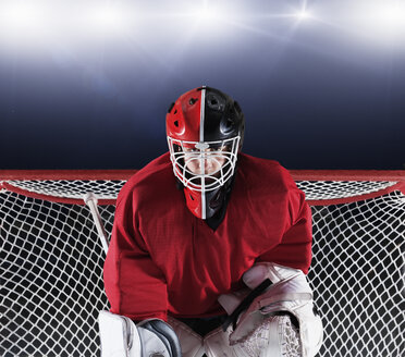 Portrait determined hockey goalie protecting goal net - CAIF11150