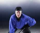 Portrait determined hockey player in blue uniform on ice - CAIF11153