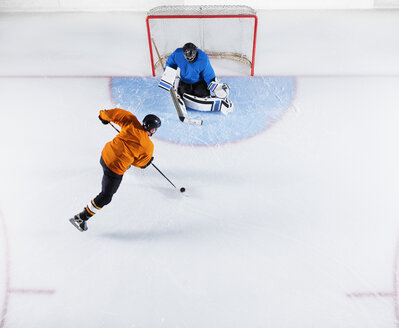 Hockey player shooting the puck at goal net - CAIF11159