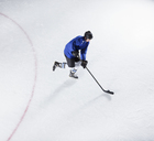 Hockey player in blue uniform skating with puck on ice - CAIF11168