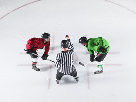 Hockey referee initiating opening face off between opponents - CAIF11171