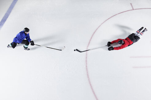 Overhead view hockey players diving for puck on ice - CAIF11177