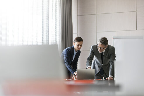 Businessman and businesswoman using laptop in conference room - CAIF11183
