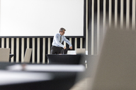 Businessman placing jacket on chair in conference room - CAIF11198