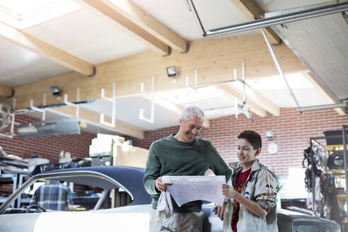 Father and son reviewing plans in auto repair shop - CAIF11210