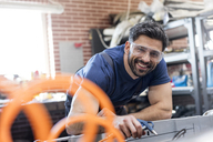 Portrait smiling mechanic working in auto repair shop - CAIF11234