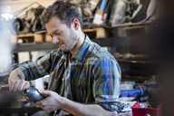 Mechanic fixing car part in auto repair shop - CAIF11240