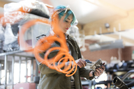 Young female mechanic with blue hair using equipment in auto repair shop - CAIF11243