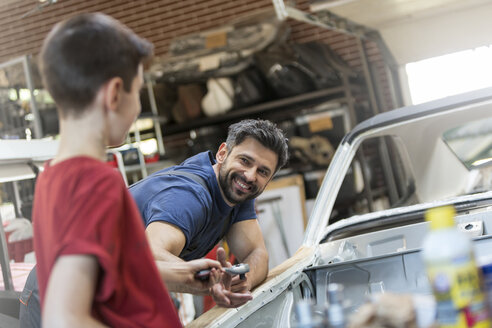Smiling father taking tool from son in auto repair shop - CAIF11252