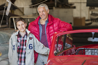 Portrait smiling father and son next to classic car in auto repair shop - CAIF11258