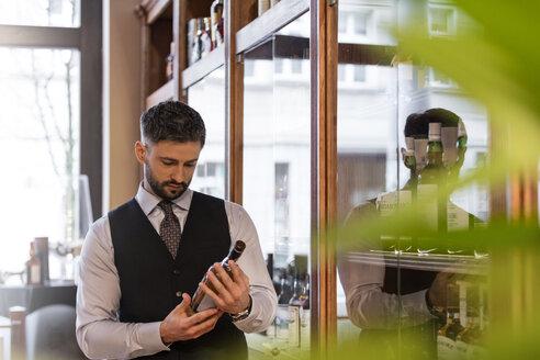 Well-dressed bartender examining whiskey bottle - CAIF11279