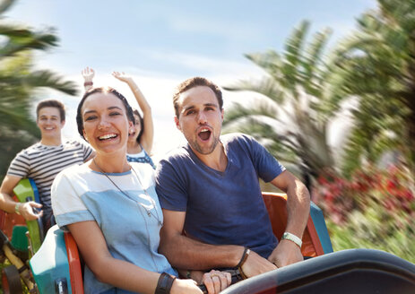 Young couple cheering on amusement park ride - CAIF11300