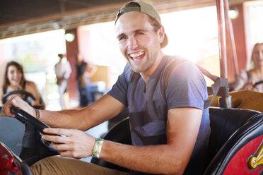 Laughing young man riding bumper cars at amusement park - CAIF11309