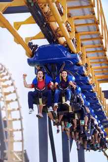 Young man cheering on amusement park ride - CAIF11315