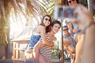 Friend photographing young couple piggybacking at amusement park - CAIF11318