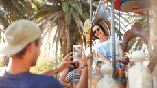 Young man photographing woman on carousel at amusement park - CAIF11321